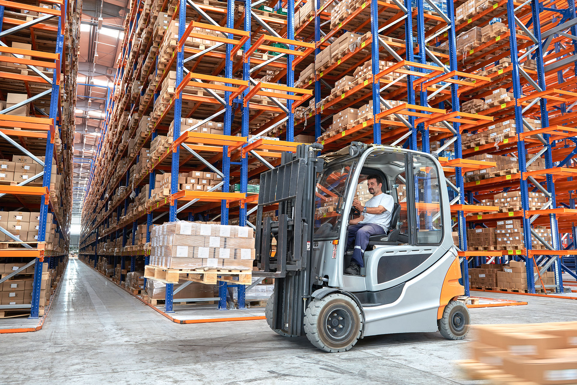 man driving a forklift in a distribution center
